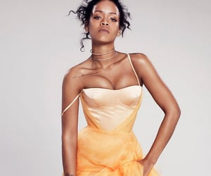Rihanna in light yellow dress with sheer flowy skirt posing for Elle magazine by photographer Paola Kudacki