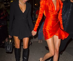 Kendall Jenner and Hailey Bieber models and friends looking amazing in orange and black outfits - image via @kendallsjbra on Twitter