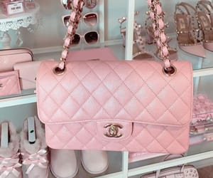 Pink Chanel handbag with pink accessories in the background