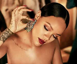 Rihanna iconic makeup look with red lipstick and amazing intricate earrings