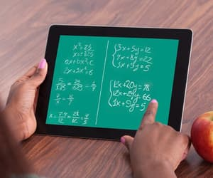 hands holding iPad show a green screen colored like a chalkboard with white math work written on it.