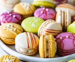 Colorful macarons, pink, red, yellow and white, with chocolate drizzle and sprinkles.