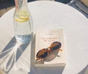 book, sunglasses, and water image