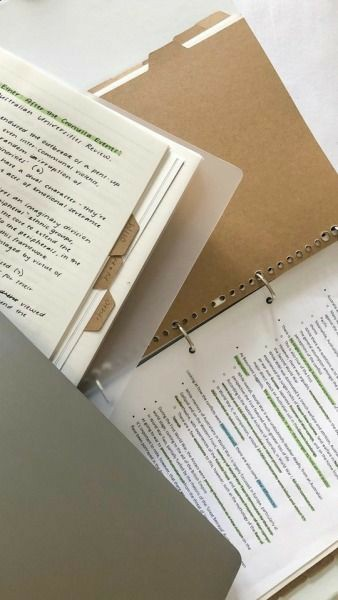 study materials such as a brown folder and a notebook containing highlighted notes