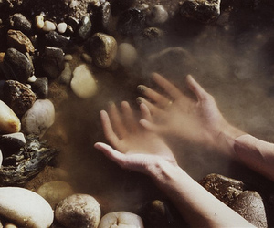 hands, water, and stone image